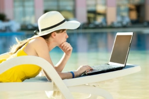 woman in a floppy hat works on her laptop by the pool during the Summer slow down. She learns SEO for therapists with an SEO specialist at Simplified SEO Consulting
