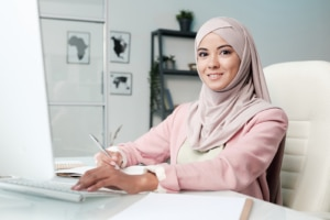 Woman in a headscarf works on her laptop in an office setting she learned 5 quick tips to boost SEO for counselors from an SEO Consultant at Simplified SEO Consulting