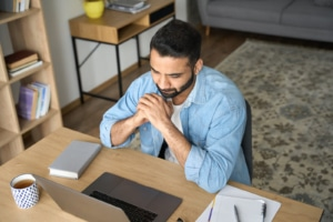 Hispanic man works on his laptop in an office setting representing working on SEO for counselors. Learn more from an SEO expert who does SEO for therapists at Simplified SEO Consulting