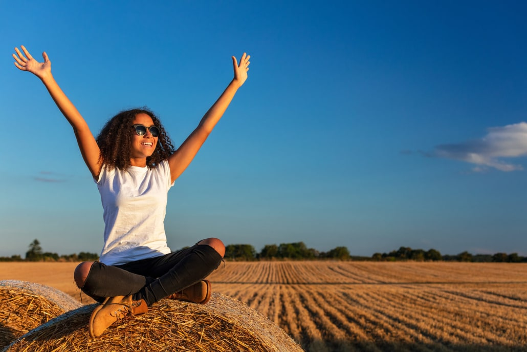 Happy woman in a field raising her hands up. She taught herself the basics of SEO for therapists to optimize her therapist website or therapy website for search engines.