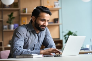 Indian man types on his laptop computer. He is a therapist working on copywriting for SEO for his private practice website. Learn more about SEO from an SEO specialist at Simplified SEO Consulting