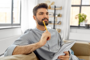 man taps a pencil to his chin while he makes a list in a notebook. He is thinking about his clients pain points when doing copywriting for SEO for his private practice website. Learn SEO from an SEO specialist at Simplified SEO Consulting